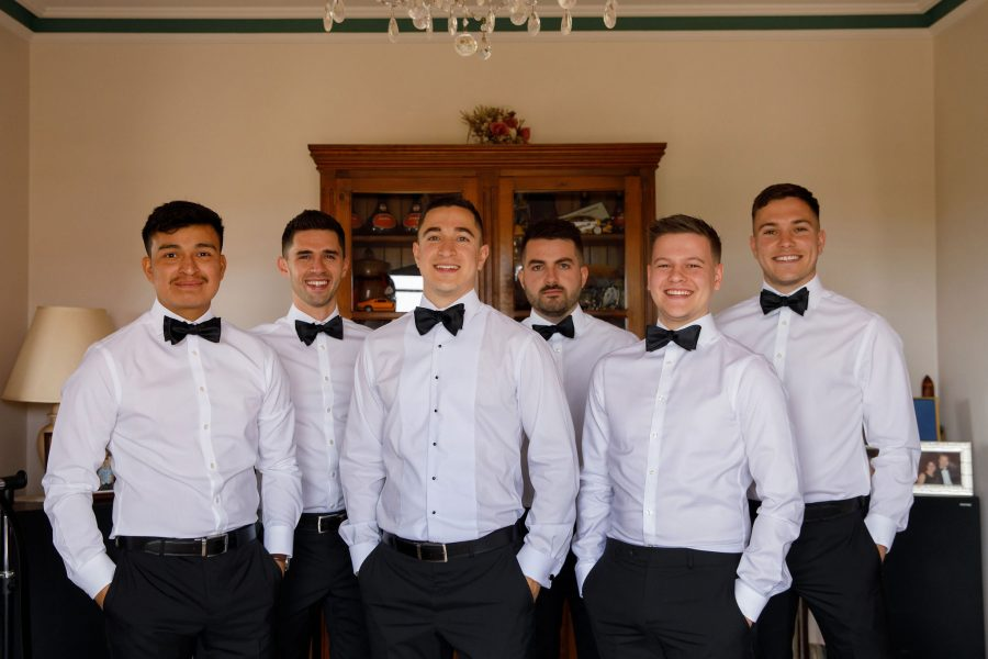 Groomsmen wearing made-to-measure tailored suits with bow-ties in Adelaide