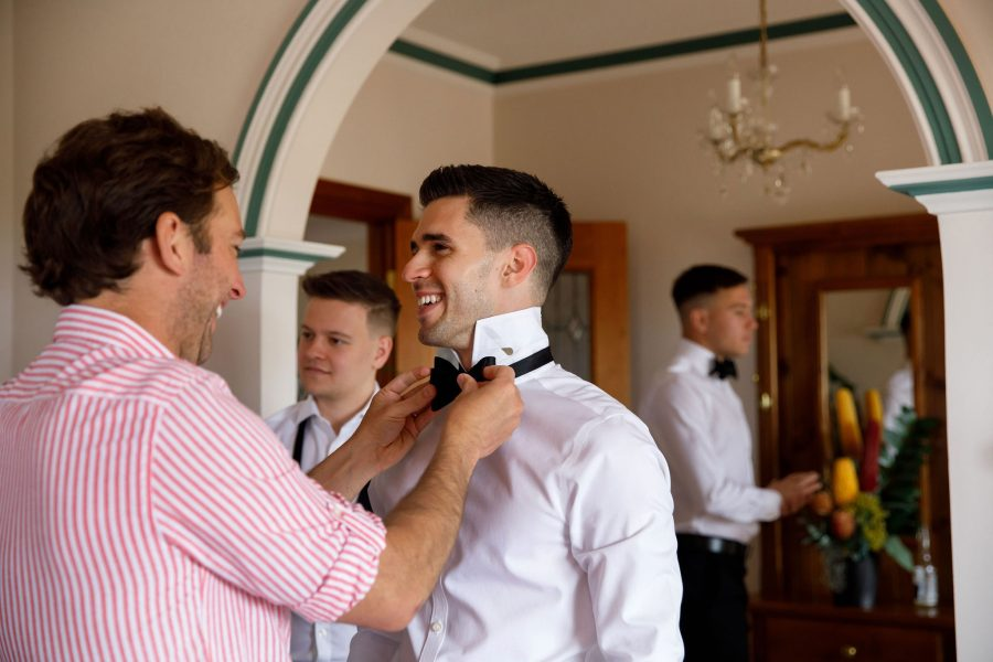 DELUCA Tailors stylist fixing the grooms bow-tie