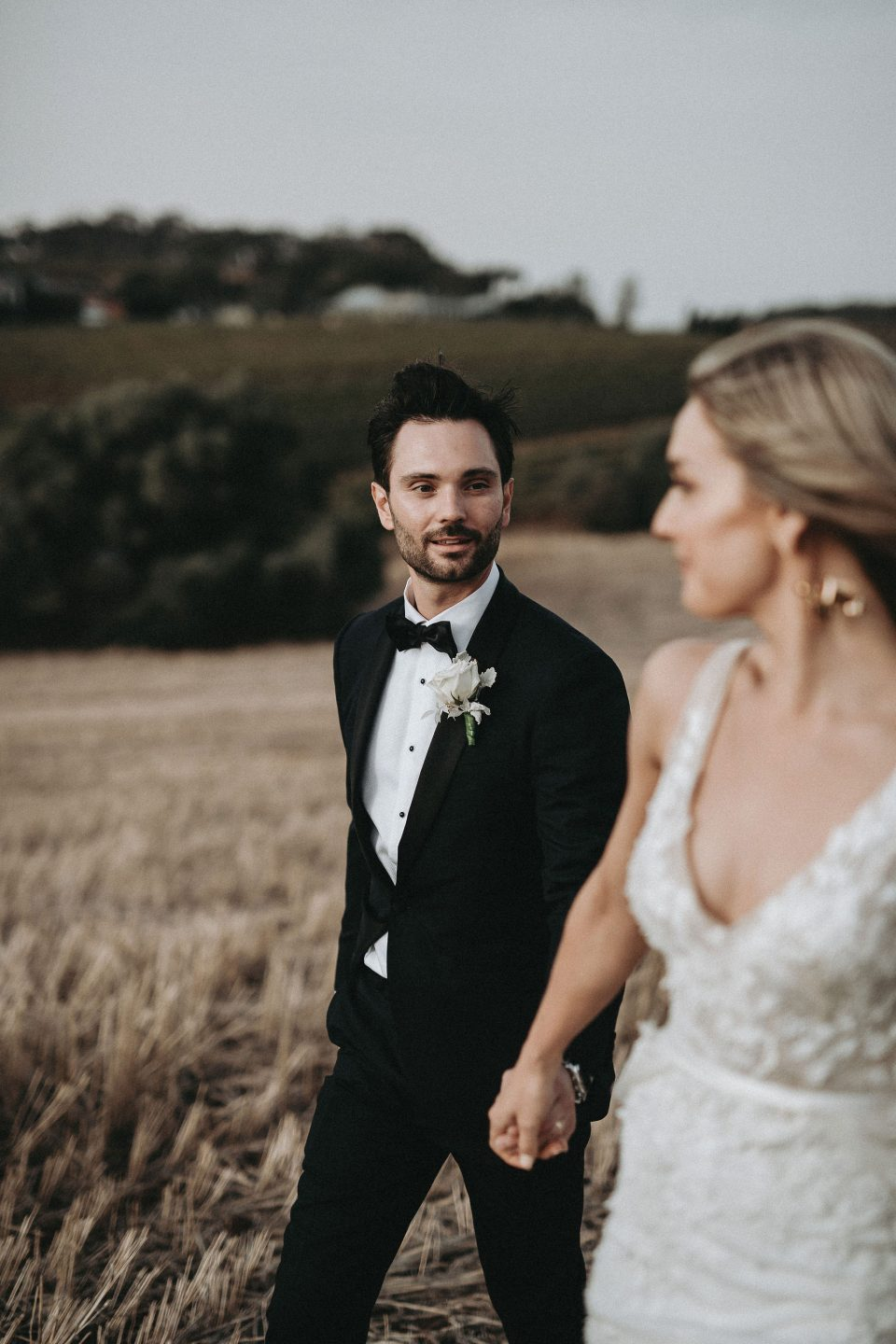 Groom wearing tailored suit looking at his bride in Adelaide