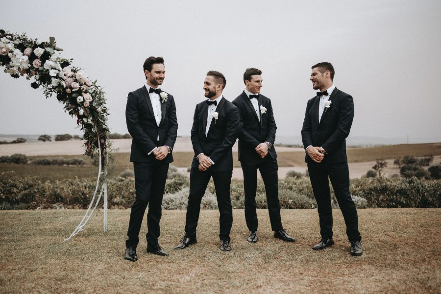 Groom standing at the altar with his groomsmen in custom made-to-measure suits