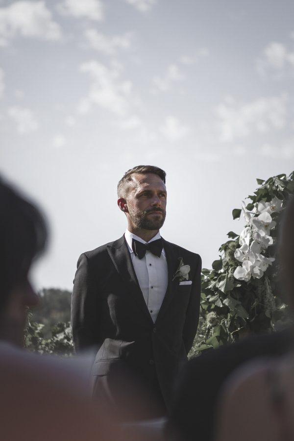 Groom at the altar wearing tailored suit